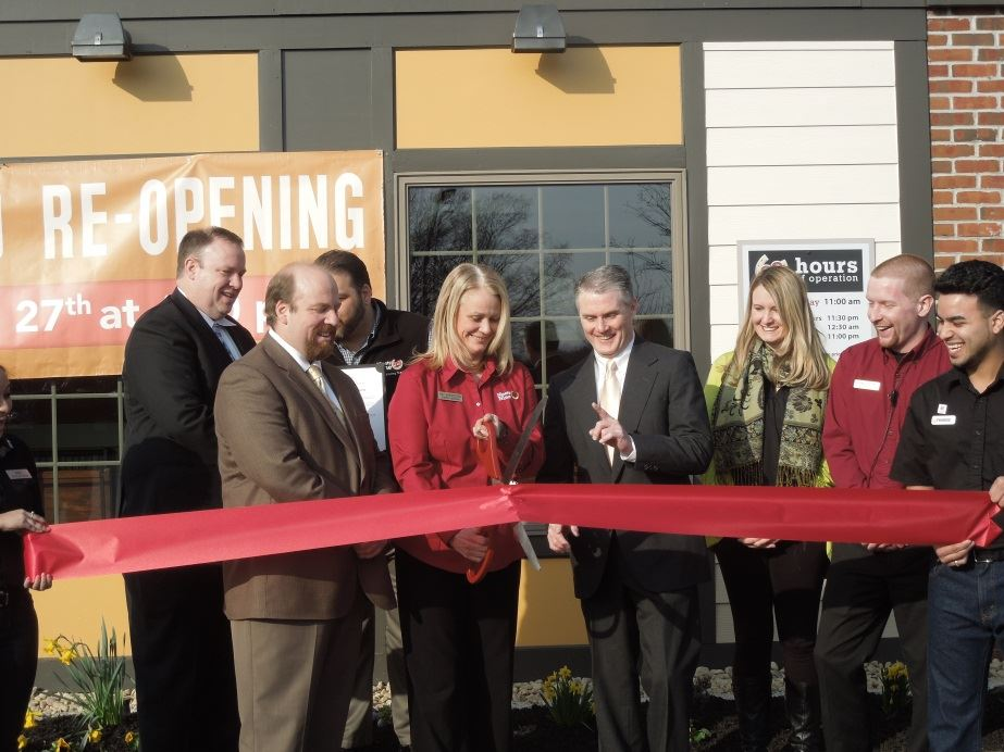 A group of people doing a ribbon cutting in front of a business