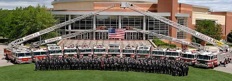 Members of the Lowell Fire Department standing in front of fire trucks and the Civic Center
